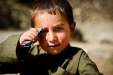 A small boy looks on as US Army soldiers and Afghan National Police search his family compound in the Jalrez Valley.