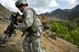 A US Army soldier scales a rocky hill.