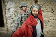 An Afghan man of Hazara descent—an ethnic group related to the Mongols who once ruled the country—spreads his arms while a US Navy sailor attached to an Army Civil Affairs team searches a passerby during a patrol in the Jalrez Valley.
