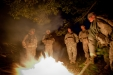 Soldiers from the 4-25 Field Artillery Regiment warm up beside a bonfire at dawn before heading out on patrol.