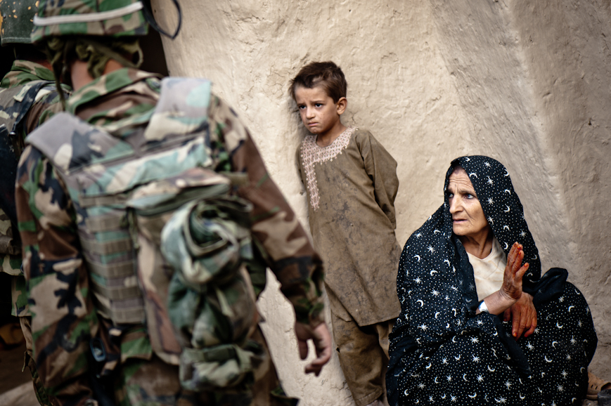An Afghan woman responds to questions from Afghan National Army soldiers during a search of her family's compound. She told the ANA and US troops that all the fighting age men left Nur Muhammad Kalache for the nearby desert town of Jelawur to find work, since the grape harvest had finished and there was no work in the village.