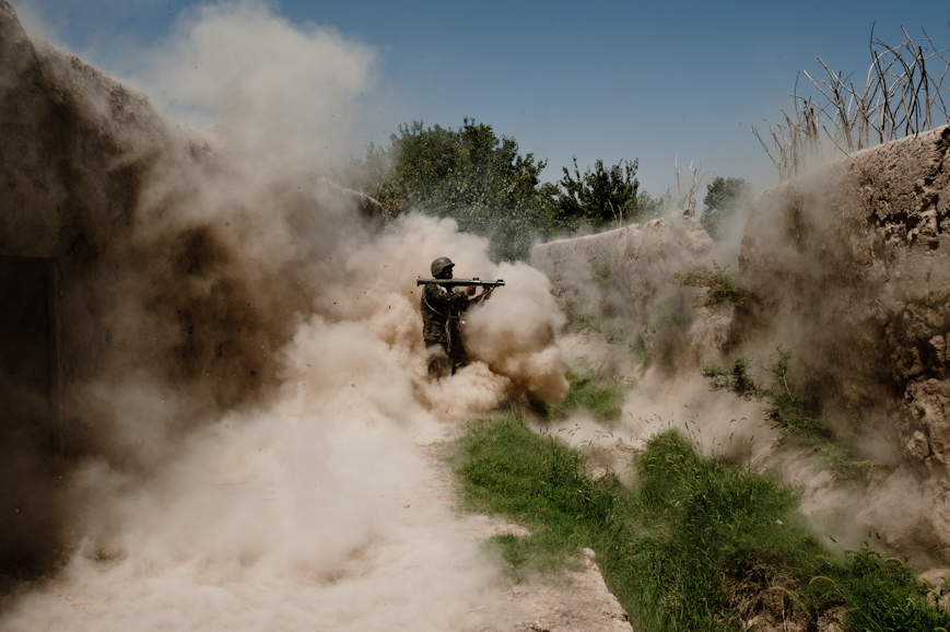 A massive dust cloud kicks up as Sherullah, and Afghan National Army soldier from Logar Province, fires his rocket-propelled grenade at an insurgent position through the notch in the wall outside the temporary patrol base in Nur Muhammad Kalache.