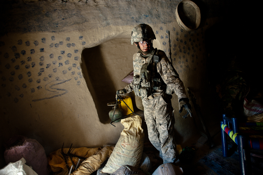 Captain Jimmy Thomasson inspects what he believes to be a cache of bomb-making materials in an empty compound in Nur Muhammad Kalache. Thomasson's team found a half-dozen bags of ammonium nitrate fertilizer—a key bomb-making material—as well as cookstoves, bits of metal used to make pressure plates, and plastic jugs used to pack explosives.
