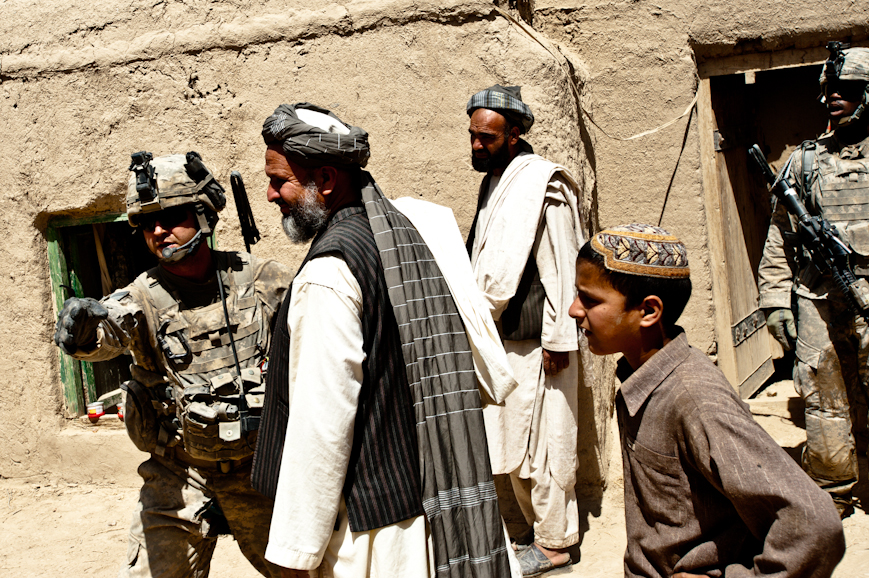 Sergeant Hunter Wilke, a team leader in Captain Aebischer's platoon, directs a villager elder in Laden Taben and his son to go home after they had been temporarily detained and questioned. Alpha Battery troops identified the man in the background, center, as related to a key Taliban sub-commander; he was detained, but later released.